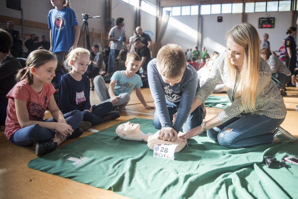 Children learning CPR from their teacher. Photo Łukasz Widziszowski